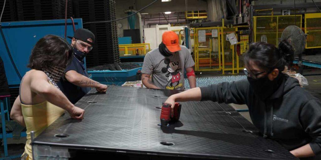 TriEnda employees working on a plastic pallet